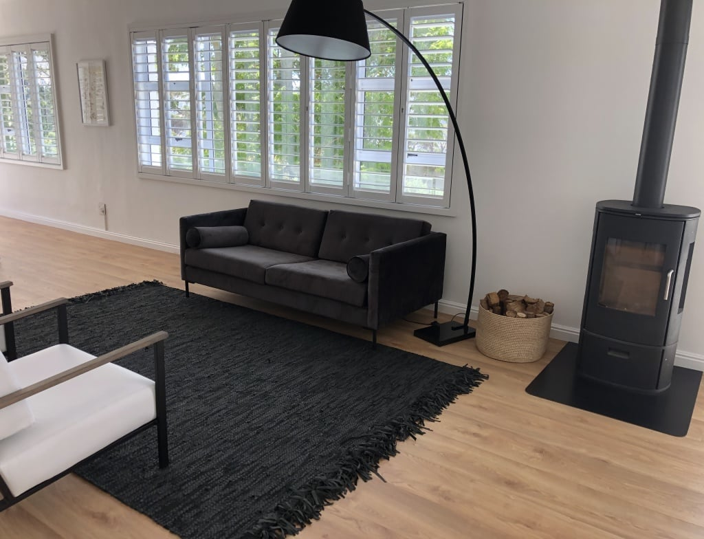 black rug on laminate floor dividing a areas space visually